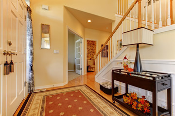 Hallway and entrance with white staircase and warm yellow walls