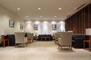 leather sofas, armchairs and tables in light, empty office