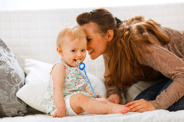 Adorable baby with soother and young mother playing on divan