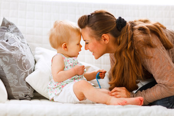 Cute baby with soother and young mom playing on divan