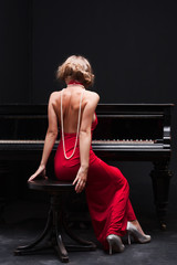 Foto op Textielframe Rood, zwart, wit beautiful young attractive woman in cocktail dress and piano