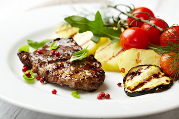 Closeup of gourmet grilled steak with grilled vegetables