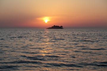 sunset behind an island