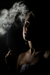 beautiful woman with a cigarette in the dark