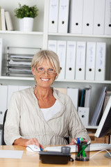 aktive ältere frau am schreibtisch