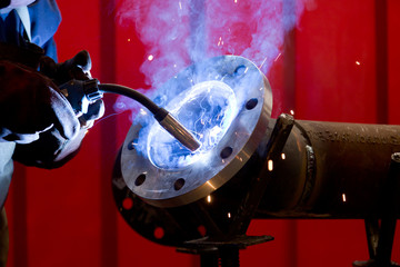 factory worker welding metal and sparks spreading