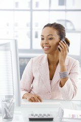 Happy businesswoman at desk on call