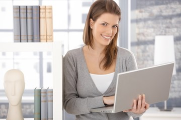 Happy woman at bookcase with computer