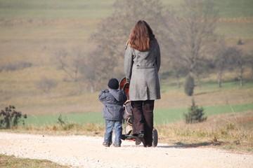 Mutter mit Kleinkind und Baby im Kinderwagen