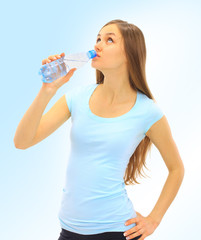 A beautiful young woman to drink the water on a