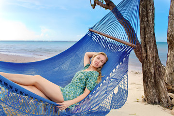 Young woman in hammock on background of palm trees and ocean