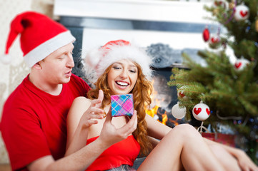 Young happy couple near a Christmas tree at home holding gift an