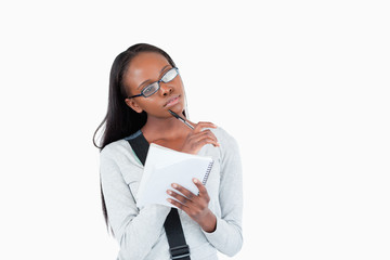 Young woman with glasses and notepad in thoughts