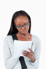 Young woman with glasses on taking notes