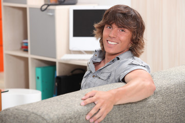 man sitting on a couch and smiling