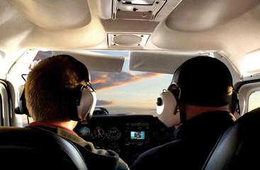 Pilot im Cockpit auf Rundflug im Sonnenuntergang