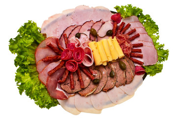 Dish with sliced ham, cheese and salami rolls and lettuce.