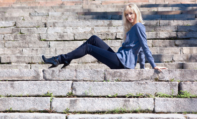 Beautiful young girl sitting on stone steps