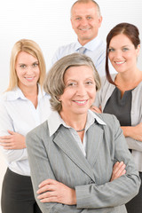 Businesswoman senior with colleagues in the back