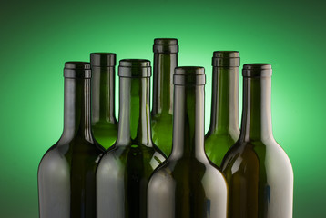 Wall Mural - Red wine bottles back lit by a green spot light