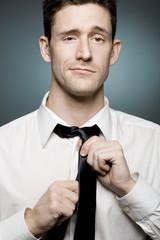Handsome confident man fixing his tie.