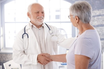 Mature doctor and senior patient shaking hands