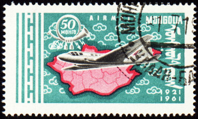 Flying air liner and map of Mongolia on post stamp