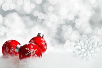 Rote Christbaumkugeln im Schnee
