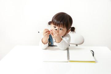 ペンをみつめる女の子