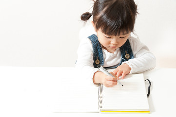 ノートに何かを書く女の子