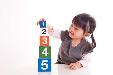 数字のブロックを積み上げる女の子