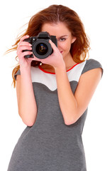 Cute young woman in gray dress with digital camera on white