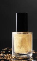 Golden nail polish on black background