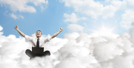 Happy young businessman with laptop sitting on the clouds.
