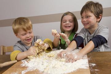 Kinder haben viel Freude beim Teig zubereiten