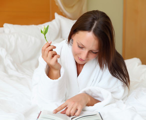young woman in bed reading a book