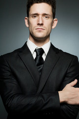Young businessman in black suit expressing confidence.