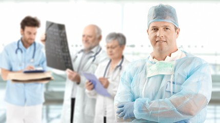 Mid-adult surgeon with medical team in background
