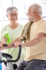 Happy elderly couple in the gym
