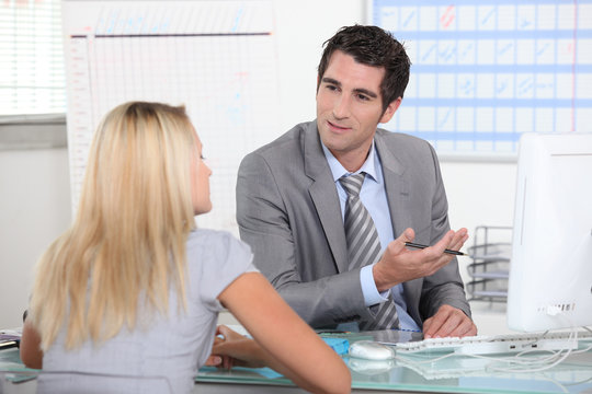 Suited man talking to a young woman across a desk