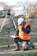 A land surveyor writing and talking on the phone