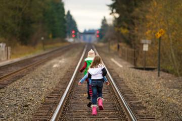 kids running down train tracks