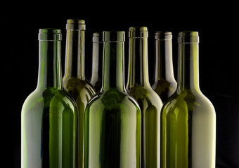 Wall Mural - Wine bottles side lit on a black velvet background