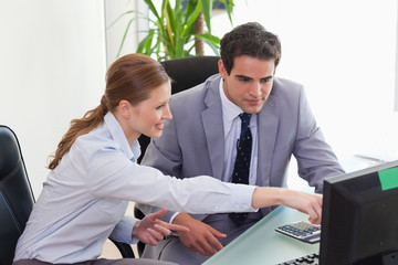 Businesswoman showing her colleague something on the screen