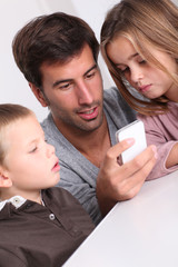Father and children playing with smartphone