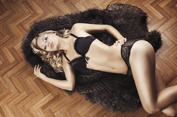 sexy girl in lingerie with fur, she has the left hand on the lef