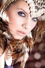 Junge Beauty Frau mit Federn Kopfputz blickt cool