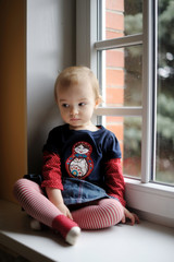 Two years old toddler girl sitting by the window