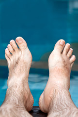 men's feet on the background of the pool