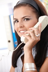 Smiling office worker on phone